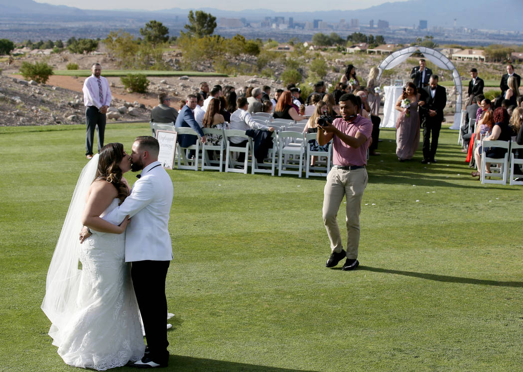 Kimberly and William King kiss after their wedding ceremony at the Revere Golf Club in Henderso ...