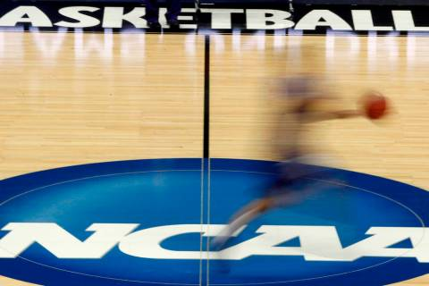 A player runs across the NCAA logo during practice at the NCAA tournament college basketball in ...