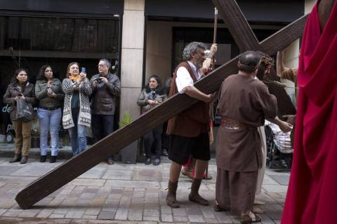 Visitors take pictures of a resident dressed as Jesus Christ during a Good Friday passion play ...