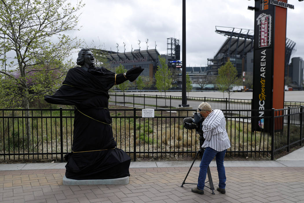 A television photographer records the partially covered statue of singer Kate Smith near the We ...