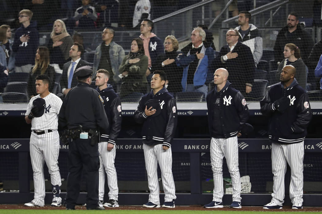 """New York Yankees players listen to """"God Bless America"""" during the seventh-inning stretch of the ..."""