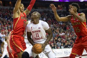 UNLV Rebels forward Cheickna Dembele (11) looks for a shot under pressure from Arizona Wildcats ...