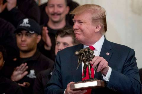 President Donald Trump holds up a statue of the Wounded Warrior Project logo presented to him d ...