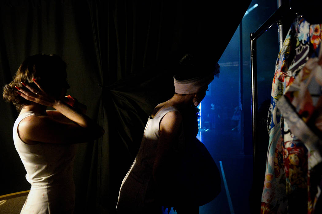 Women wait behind the curtain before going on stage for the fashion show at The Orleans during ...