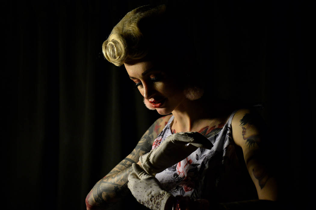 Avrora, who declined to give her last name, from Russia puts on a glove backstage at the fashio ...