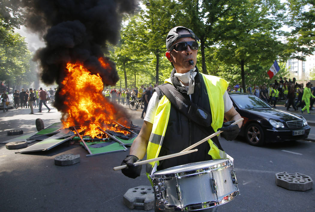 A man bangs a drum in front of a fire on the street during a yellow vest demonstration in Paris ...