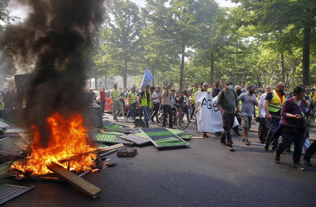 Protestors march by a burning pile of wood during a yellow vest demonstration in Paris, Saturda ...