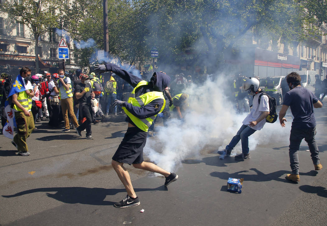 A demonstrator throws back a tear gas canister during a yellow vest demonstration in Paris, Sat ...