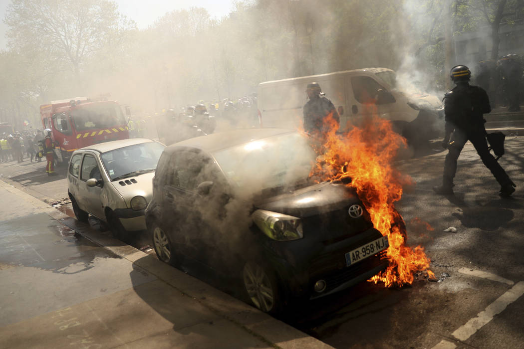 A car is set alight during a yellow vest demonstration in Paris, Saturday, April 20, 2019. Fren ...