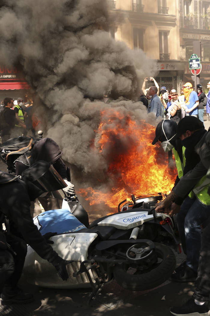 Demonstrators attend to a motorbike which was set alight during a yellow vest demonstration in ...