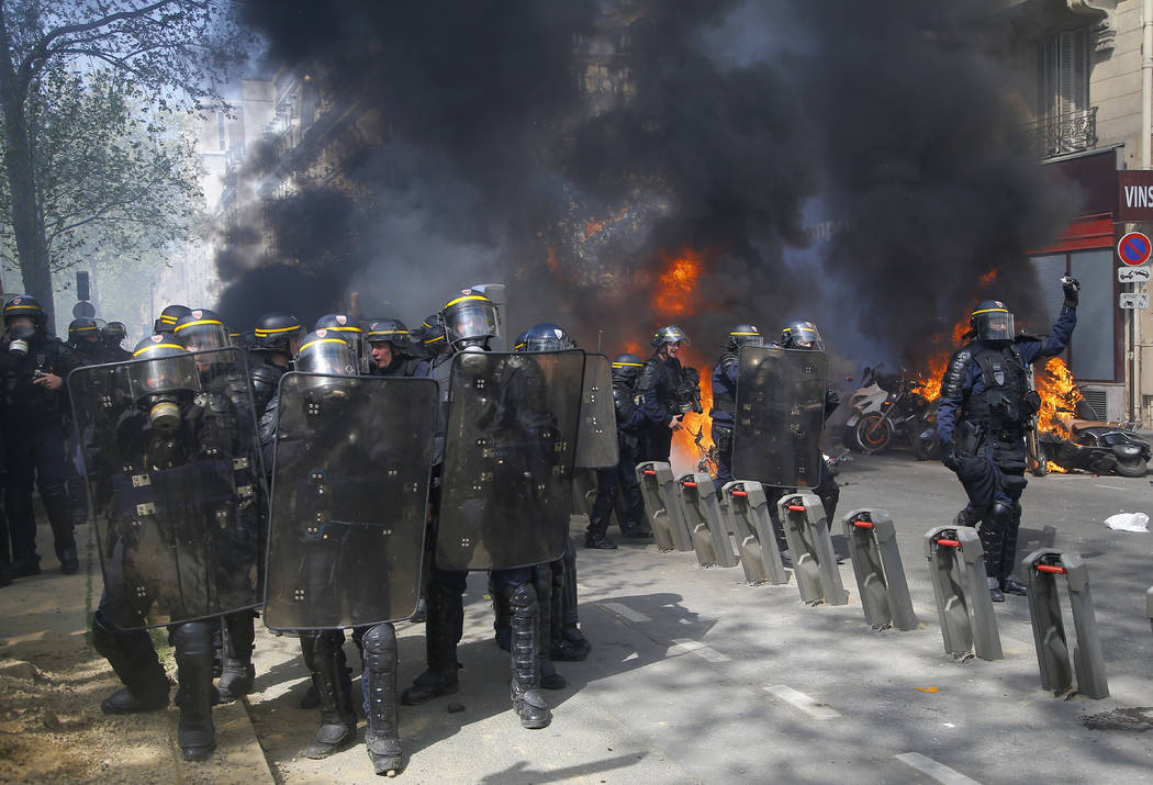 Police move in as motorbikes burn during a yellow vest demonstration in Paris, Saturday, April ...