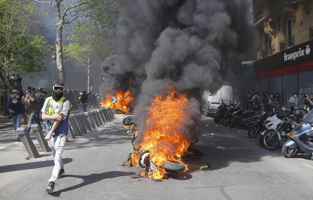 A man runs by a burning motorbike during a yellow vest demonstration in Paris, Saturday, April ...