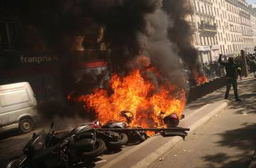 A set of motorbikes are set alight during a yellow vest demonstration in Paris, Saturday, April ...