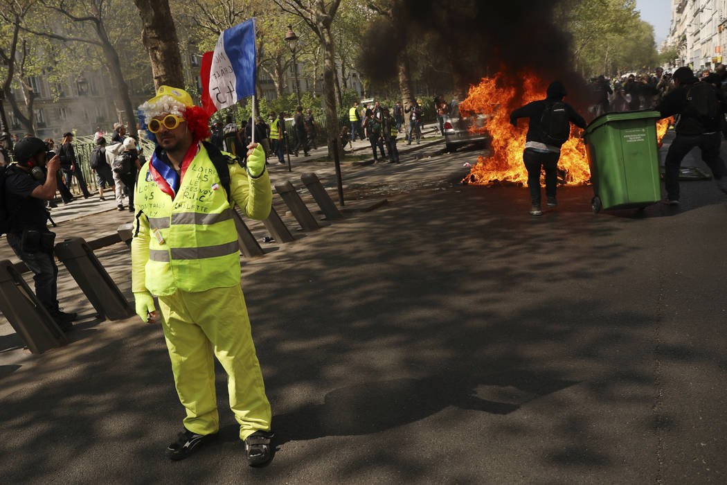 A protestors waves a French flag as a dumpster burns in the background during a yellow vest dem ...
