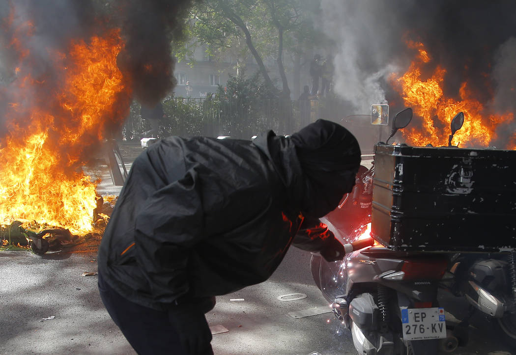 A protestor lights a motorbike on fire during a yellow vest demonstration in Paris, Saturday, A ...