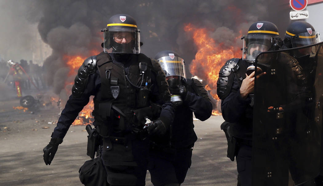 Police walk among burning vehicles during a yellow vest demonstration in Paris, Saturday, April ...