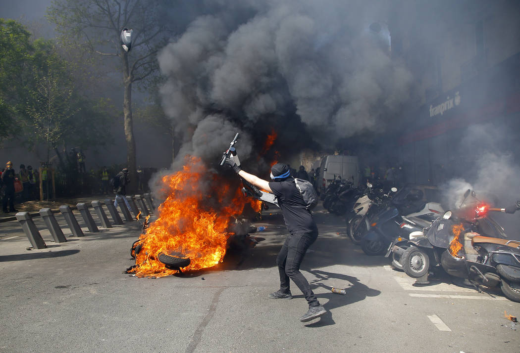 A protestor throws a scooter onto a pile of burning motorbikes during a yellow vest demonstrati ...