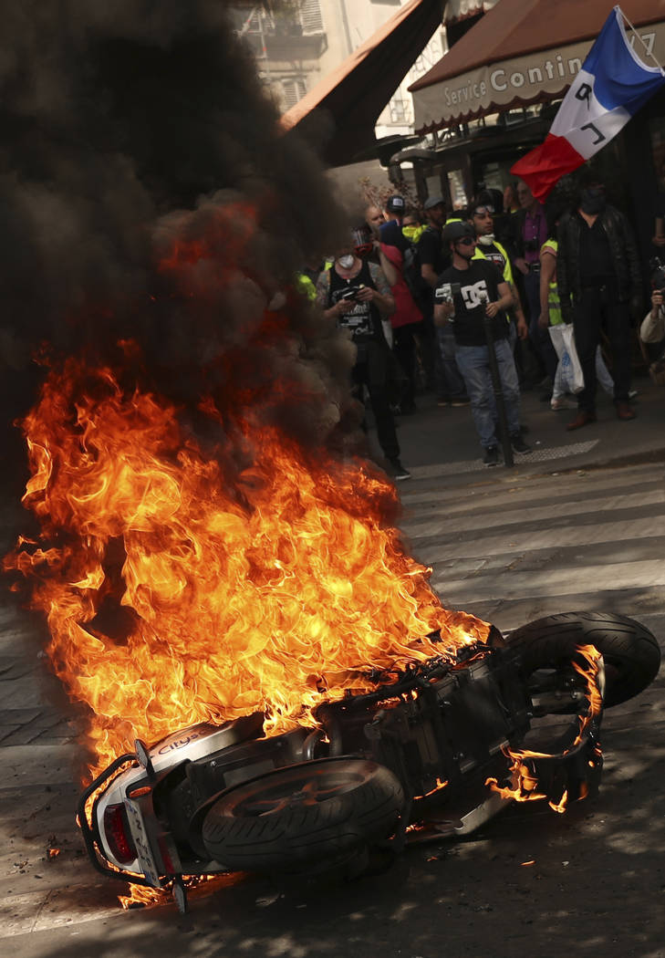 A protestor waves a French flag as a motorbike is set alight during a yellow vest demonstration ...