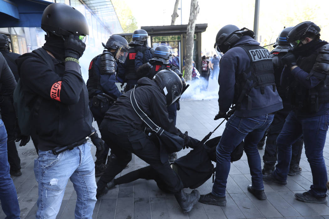 Police detain a protestor during a yellow vest demonstration in Paris, Saturday, April 20, 2019 ...