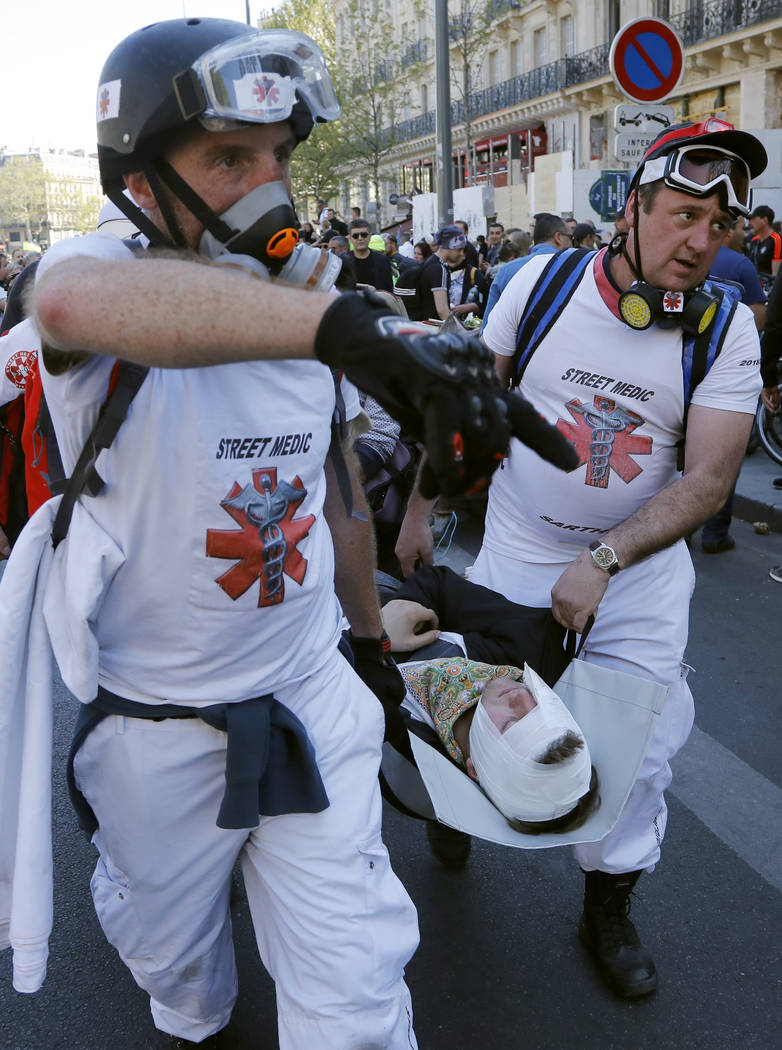 Street medics take away an injured man at Place de Republique during a yellow vest demonstratio ...