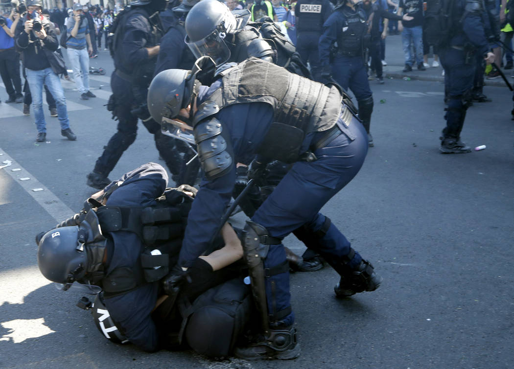 Police tackle a TV cameraman at the Place de Republique during a yellow vest demonstration in P ...
