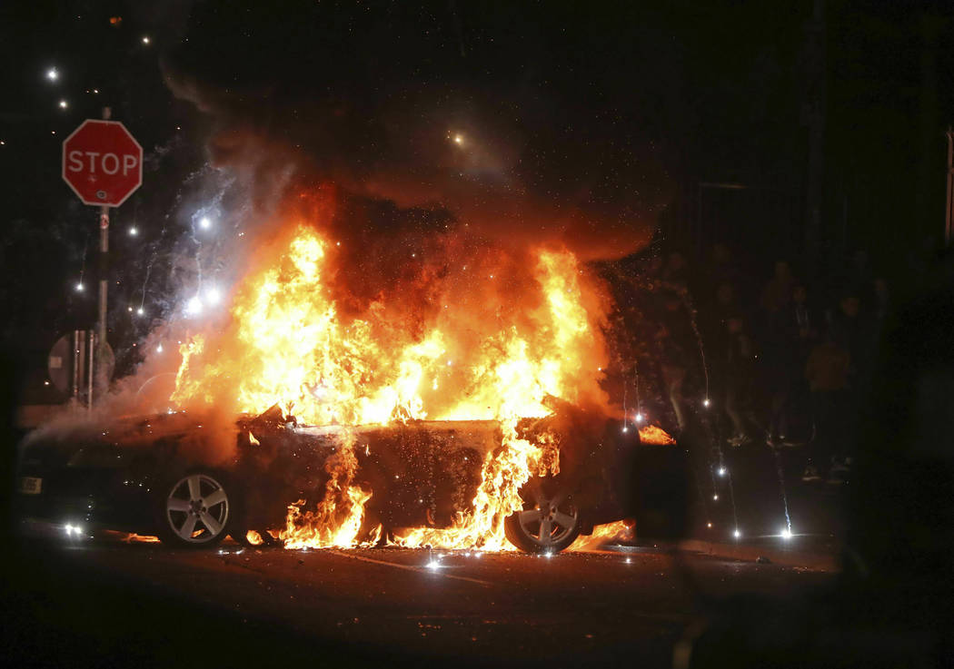 A car burns after petrol bombs were thrown at police in the Creggan area of Londonderry, in Nor ...