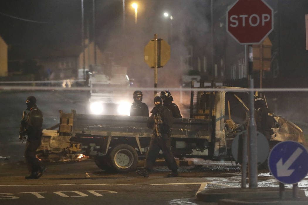 Police guard a crime scene during unrest in the Creggan area of Londonderry, in Northern Irelan ...
