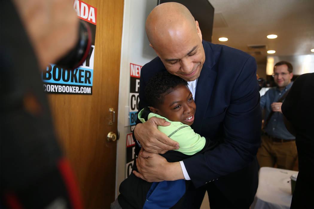 Democratic presidential candidate Sen. Cory Booker, D-N.J., hugs Jeremiah Daniels, 9, during an ...