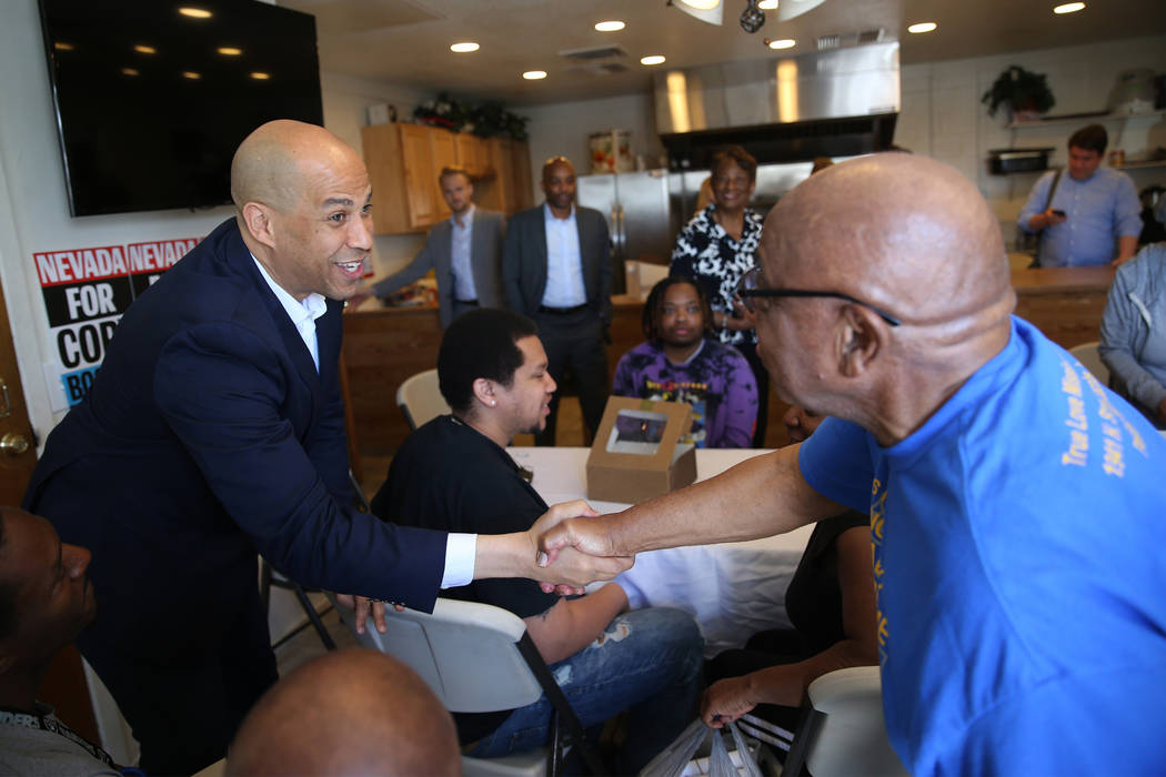 Democratic presidential candidate Sen. Cory Booker, D-N.J., left, meets the Rev. James Kelly du ...