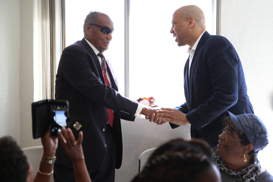 Democratic presidential candidate Sen. Cory Booker, D-N.J., right, shakes hands with the Rev. W ...