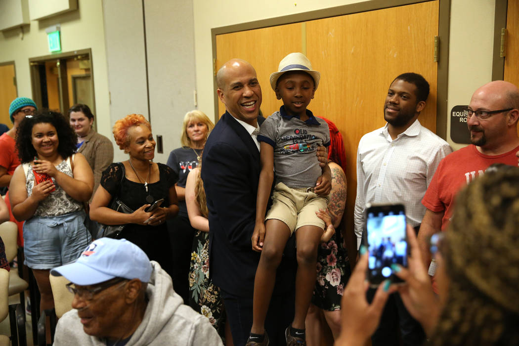 Democratic presidential candidate Sen. Cory Booker, D-N.J., center, takes a photo with Justice ...