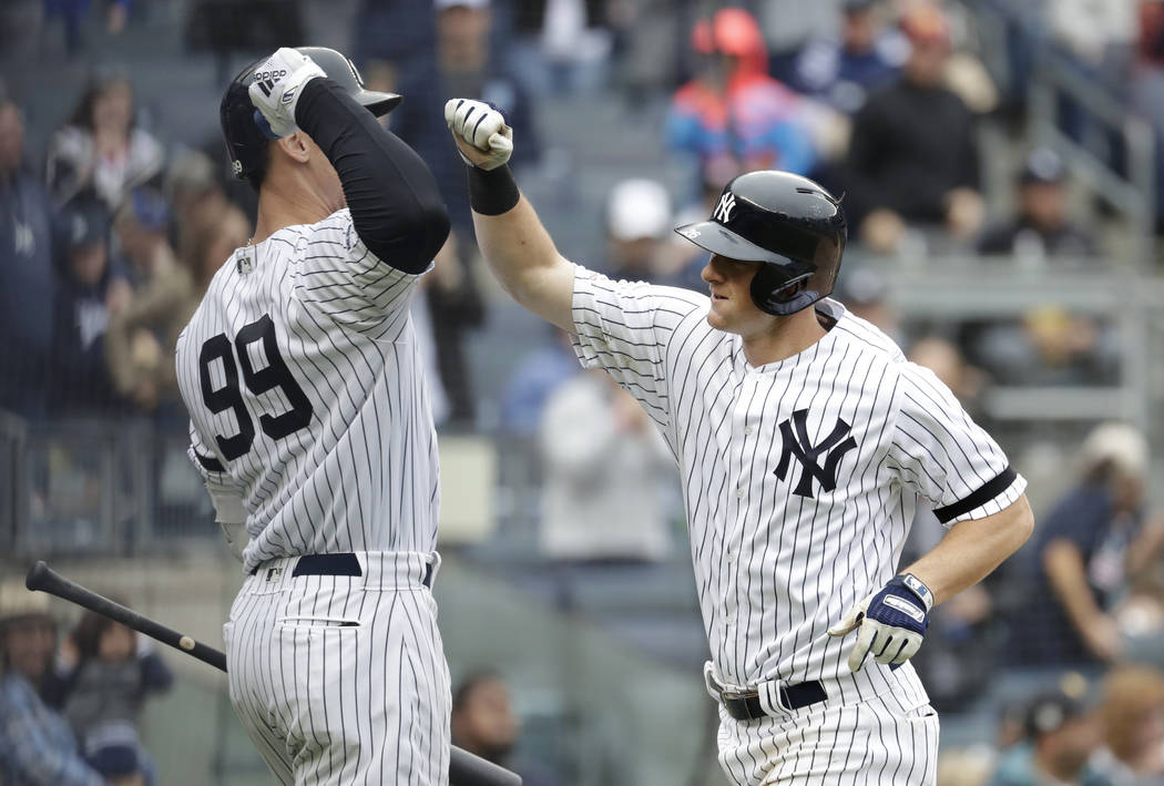 New York Yankees' DJ LeMahieu, right is greeted near the dugout by Aaron Judge (99) after hitti ...