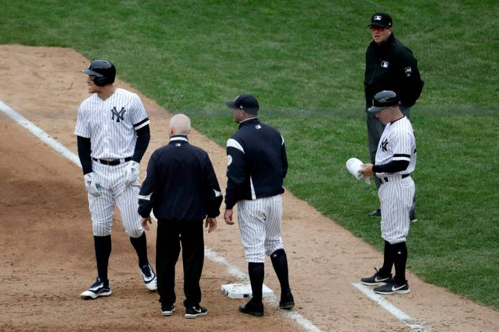 New York Yankees' Aaron Judge, left, reacts while talking to a trainer and bench coach Josh Bar ...