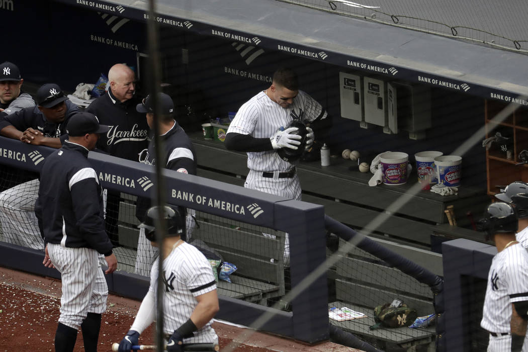 New York Yankees' Aaron Judge, center, clenches his helmet while walking in the dugout after he ...