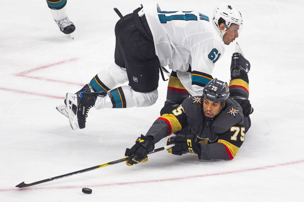 Golden Knights right wing Ryan Reaves (75) is taken to the ice by San Jose Sharks defenseman Ju ...