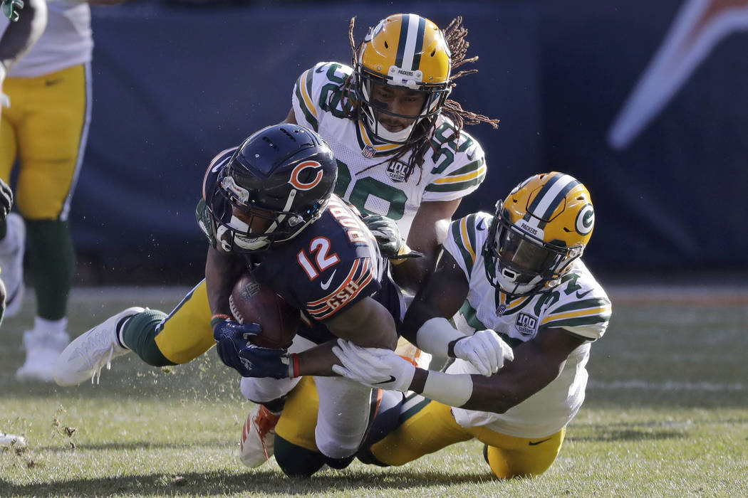 Chicago Bears wide receiver Allen Robinson (12) is tackled by Green Bay Packers cornerbacks Tra ...