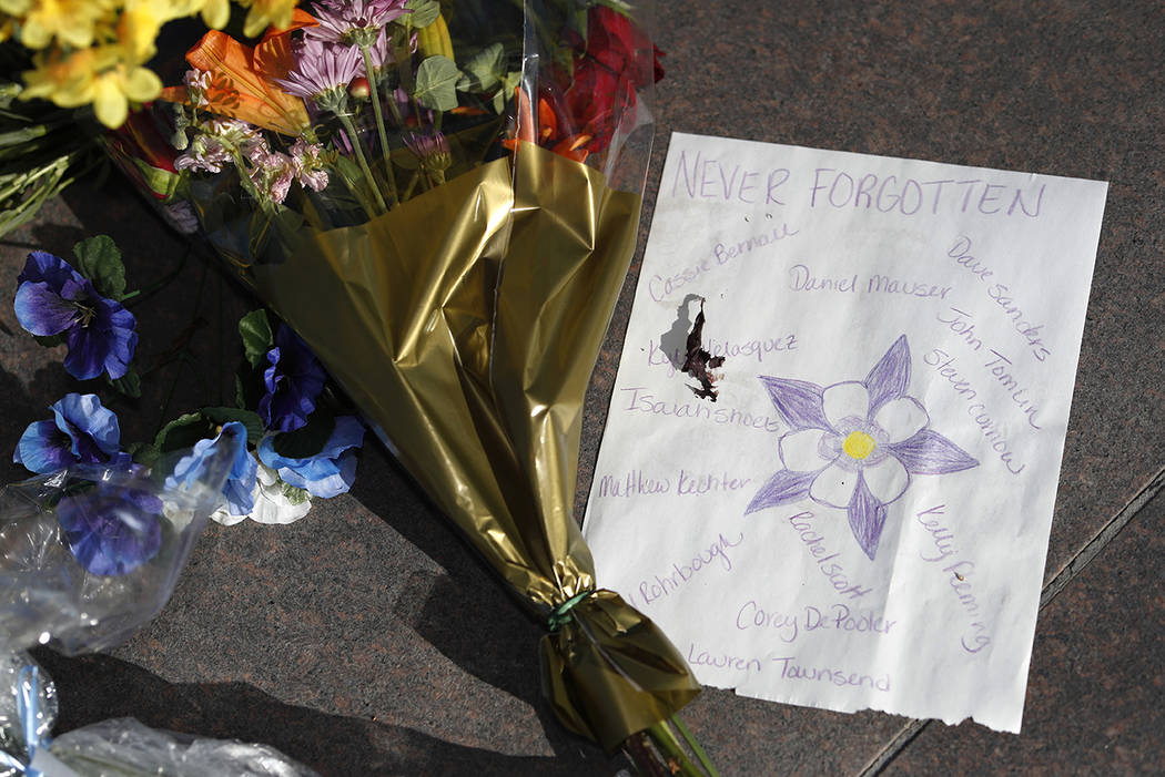 A bouquet of flowers lies next to a piece of paper bearing the names of the victims of the mass ...