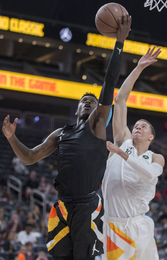 Rocket Watts (1) slices to the rim past Samuell Williamson (10) in the first half during the Jo ...