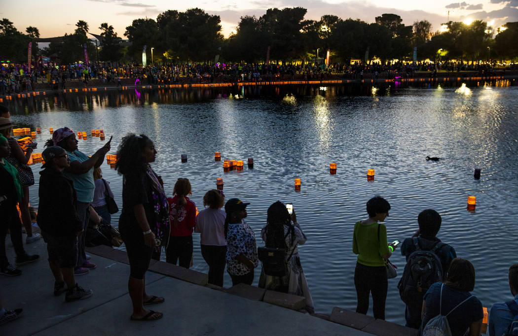 Lanterns float across the pond as people watch during the Water Lantern Festival at Sunset Park ...