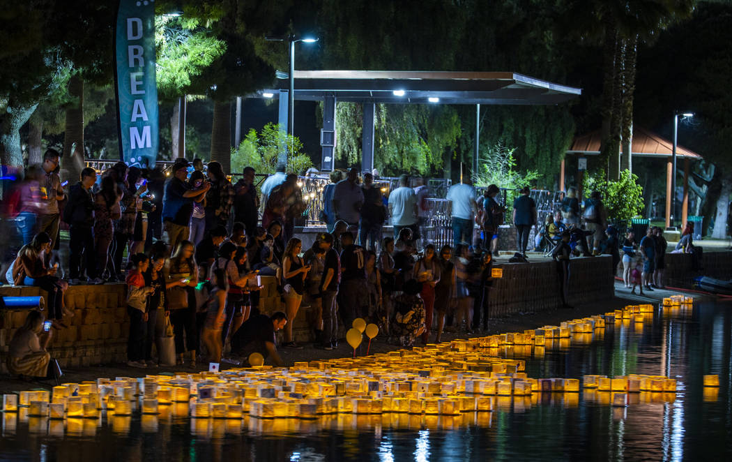 Participants stream down to the lake to launch lanterns during the Water Lantern Festival at Su ...