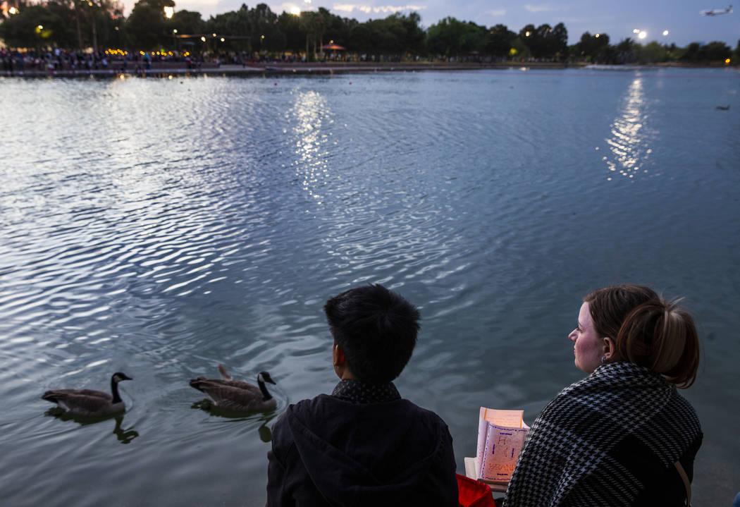 A couple look out over the lake as launching time nears during the Water Lantern Festival at Su ...