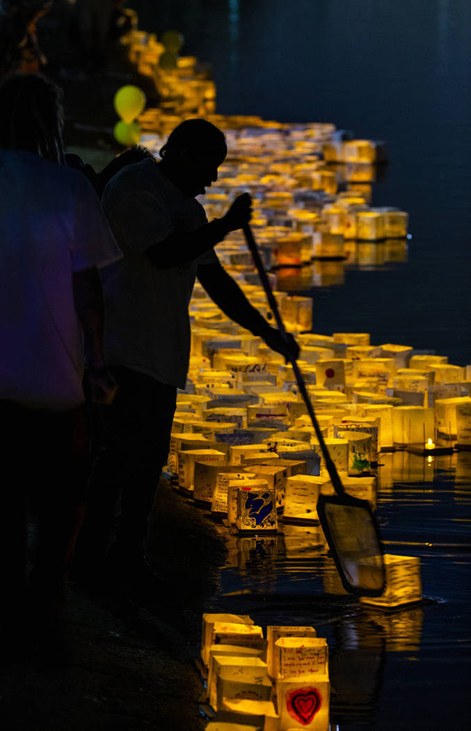 Lanterns are pushed into the lake as strong winds kept them near the shore during the Water Lan ...