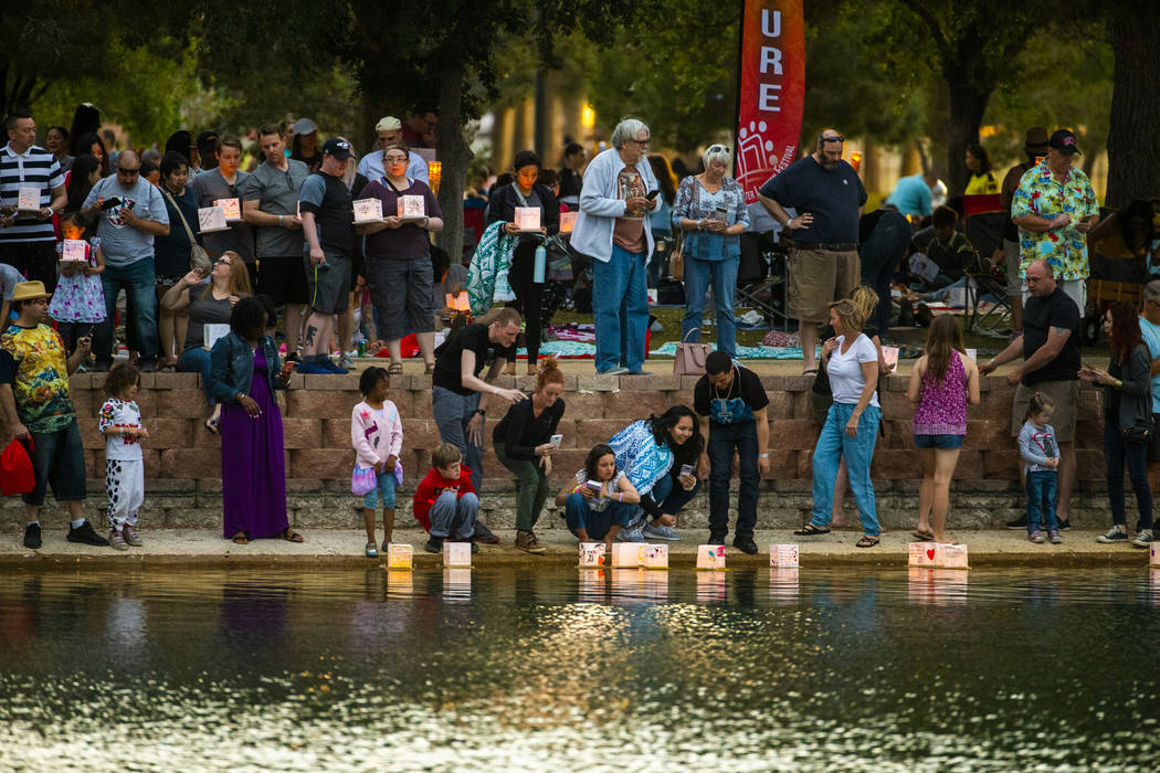 Participants gather at the lake edge to launch their lanterns during the Water Lantern Festival ...