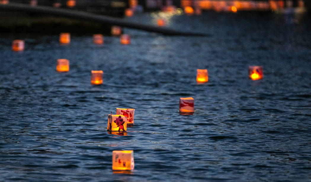 Lanterns float across the lake during the Water Lantern Festival at Sunset Park on Saturday, Ap ...