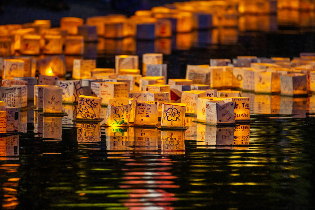 Lanterns gather near the lake edge as strong wings push them back during the Water Lantern Fest ...