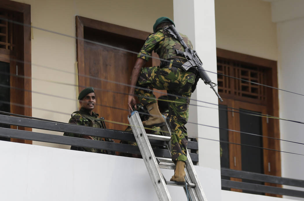 A Sri Lankan police commando enters a house suspected to be a hideout of militants following a ...
