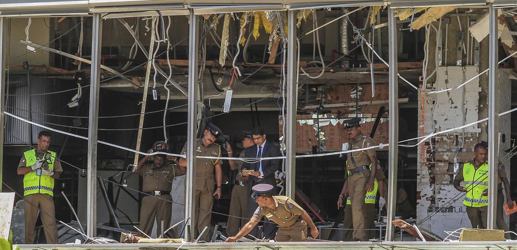 A Sri Lankan Police officer inspects a blast spot at the Shangri-la hotel in Colombo, Sri Lanka ...