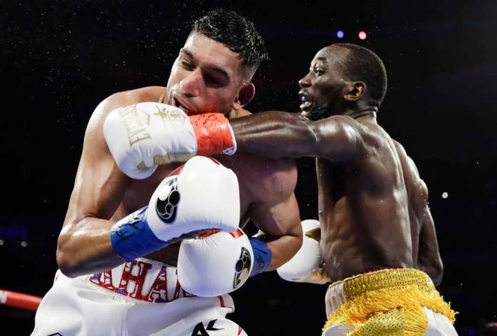 Terence Crawford, right, punches England's Amir Khan during the fifth round of a WBO world welt ...