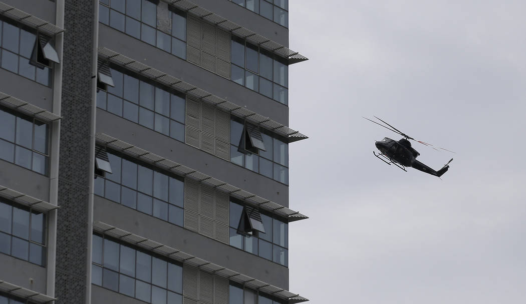 A Sri Lankan airforce helicopter flies over a house suspected to be a hideout of militants fol ...