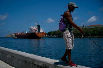 A fisherman walks on the Malecon seawall where an oil tanker can be see in the background in Ha ...
